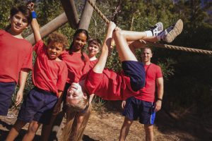Kids climbing a traverse rope during obstacle course training